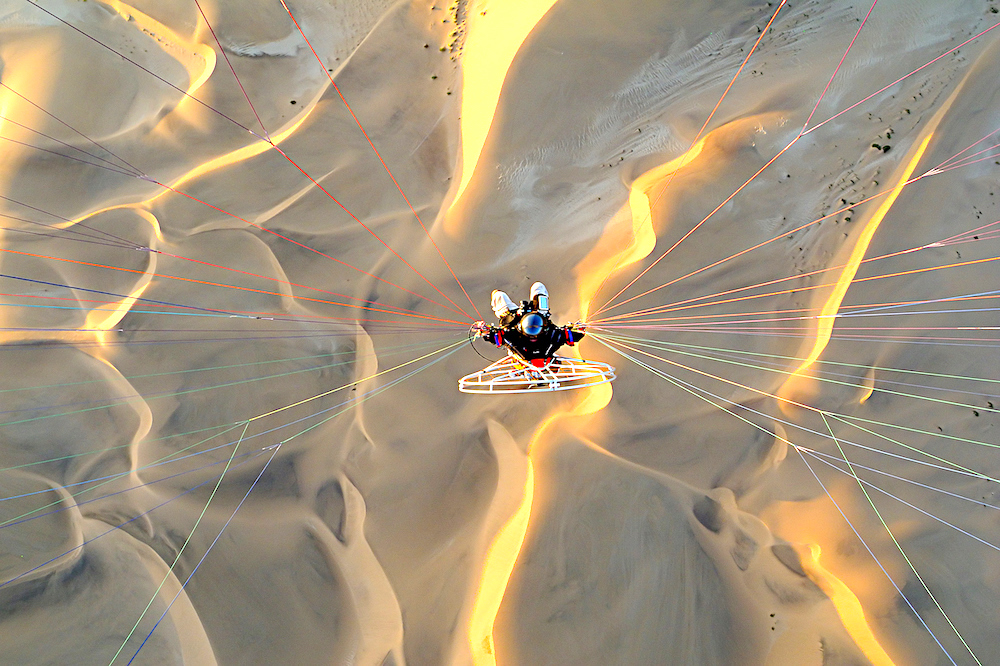 Powered paraglider flying over sand dunes